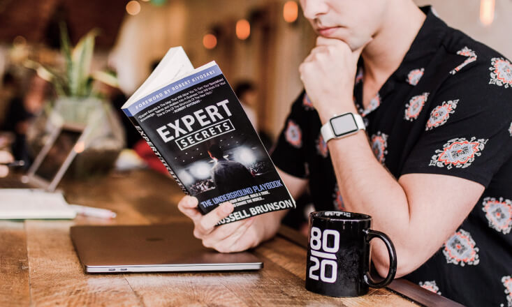 Person reading Expert Secrets book